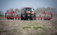 A red tractor pulling a red planter plants row crops at Felt Family Farms in Iowa