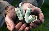 拿着金钱的农夫在他的手上。