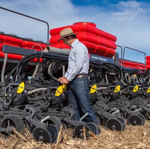 A Brazilian farmer adjusts a row unit on a planter.